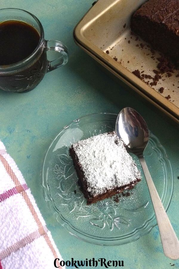 Low Carb Chocolate Coconut Flour cake slice served on a plate with icing on top, served with Black coffee.