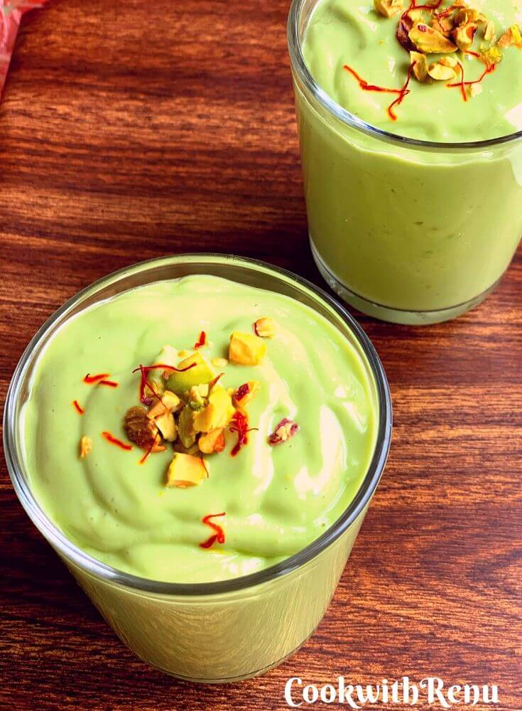Closer look of thick, creamy and green colour, Indian Style Avocado Lassi, garnished with chopped pistachio and saffron strands