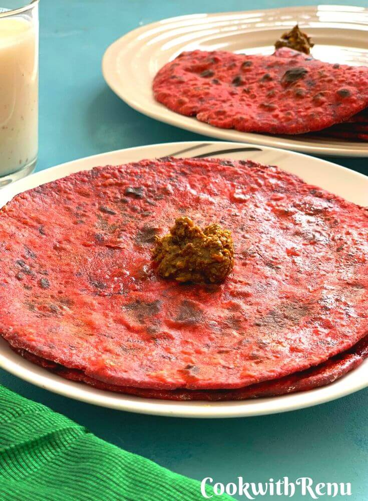 Closer look of the Red and Bright Beetroot Paratha, served with a dollop of a, chaar , dry vegetable and Buttermilk