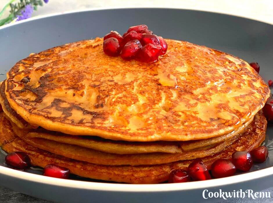Buckwheat Sweet Potato Pancakes, layered one above the other with a drizzle of maple syrup and garnished with pomegranate