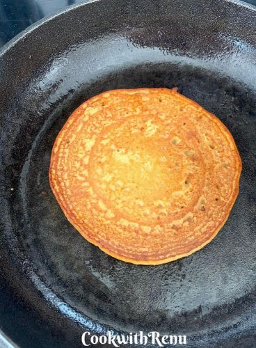 The bottom side of pancake being cooked, and the earlier side which was down is cooked