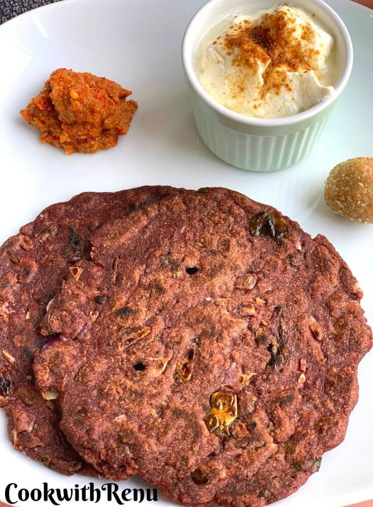 Close up look of Ragi Roti Breakfast Thali served with yogurt, garlic chutney , til ladoo