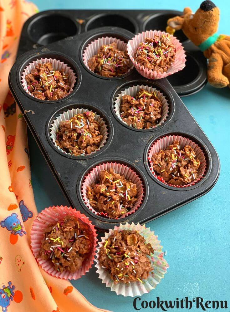 Crunchy Chocolate Cornflakes Cakes Arranged in a muffin tray and few on top. They are served with sprinklers on top and with a cute little soft toy