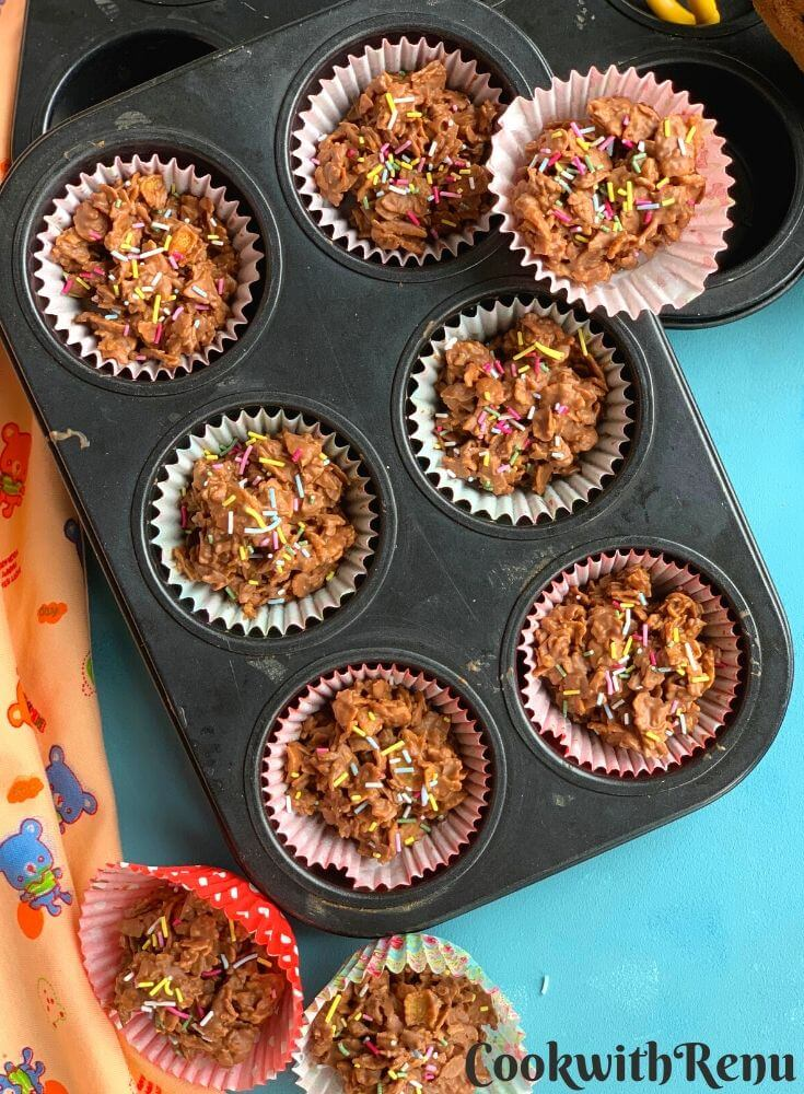 Crunchy Chocolate Cornflakes arranged in a muffin tray and few on top. They are served with sprinklers on top