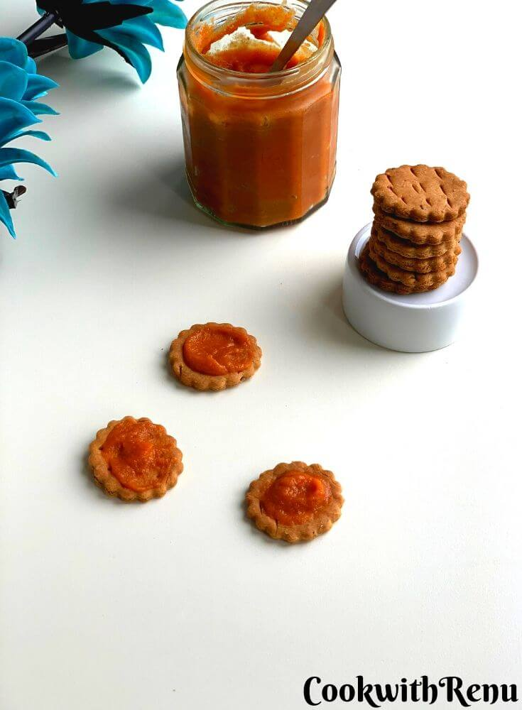 Lehsun Chutney being spread on three baked matri and presented in a glass jar. There is also a stack of baked matri on a bowl