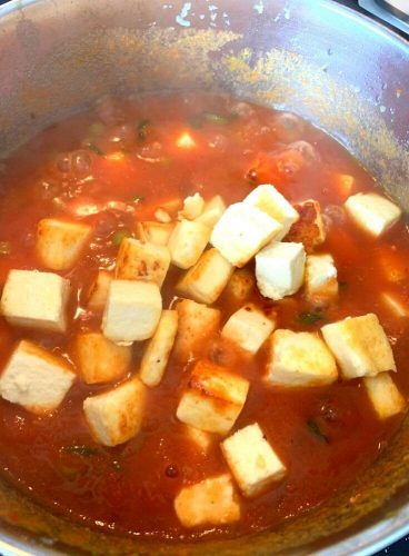 Shallow fried Paneer Cubes being added to gravy