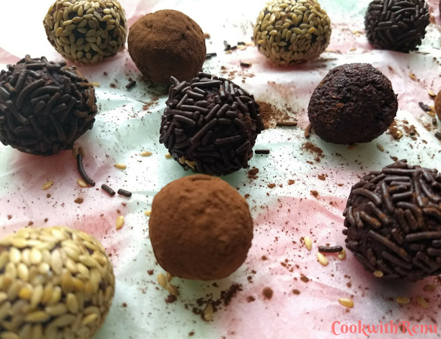 Beetroot and Dates Energy bites coated with chocolate vermicelli, cocoa powder and sesame seeds, spread on a parchment paper