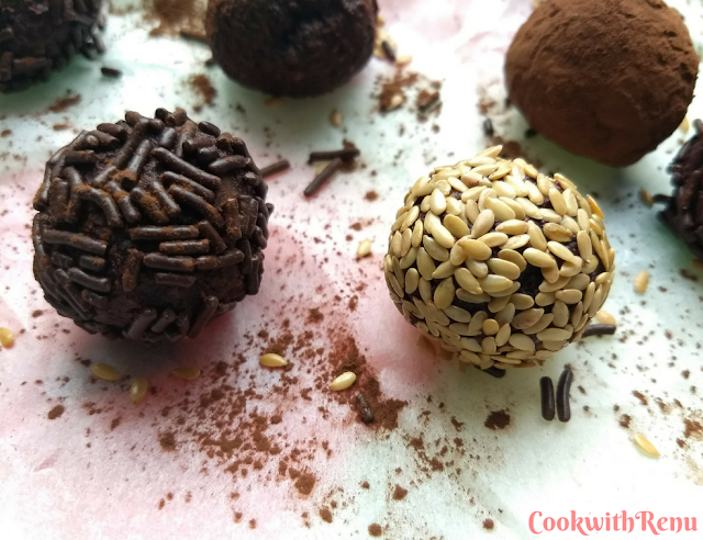 Close up look of Energy bites coated with chocolate vermicelli and sesame seeds, spread on a parchment paper