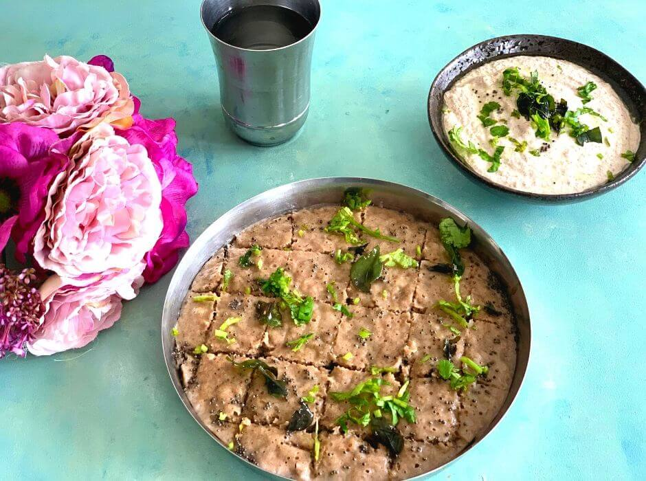 Steamed Farali Kuttu aur Singhare ke atte ka dhokla seen in a steel plate, with the tempering of mustard seeds, corainder and curry leaves, with peanut chutney as a side. Water and some flowers are seen on the side.