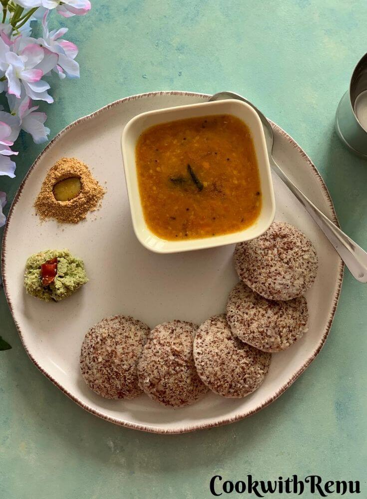 5 Ragi Idlis presented in a cream serving plate, with green coriander chutney, Idli podi and sambar. Seen in the background are some flowers and a glass of water