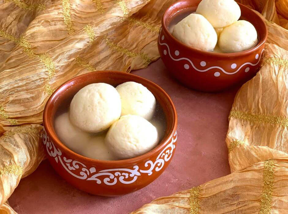 Soft and Spongy Rasgulla presented in a 2 brown bowls, with a stole on the side for presentation