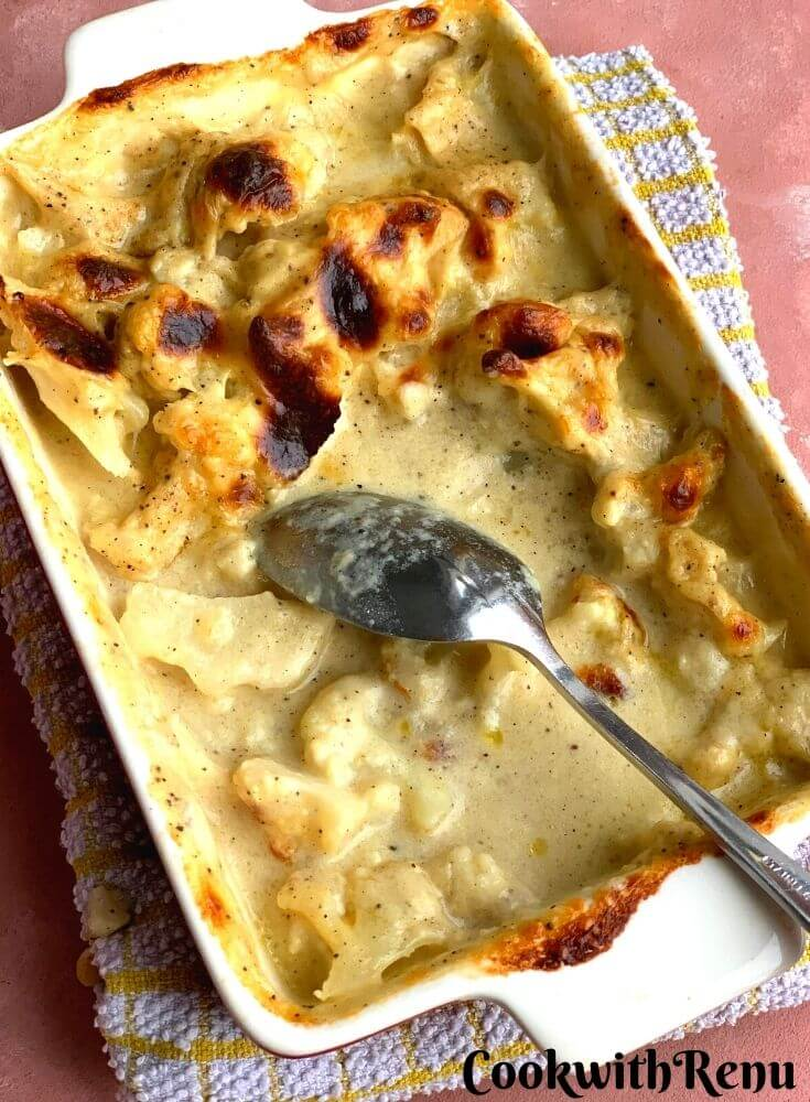 Cauliflower gratin cooked and presented in a dish with a kitchen towel under. The top looks perfectly brown and crusted well. Half of it is served.