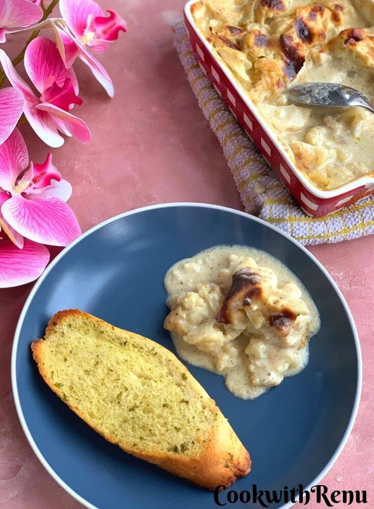 Cauliflower gratin cooked and presented in a dish. A portion is served with garlic bread on the side