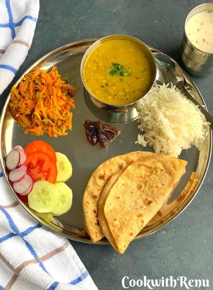 A North Indian Vegetarian lunch thali which has Roti, Steamed Rice, Oil free Lemon Pickle, Whole Green Moong Dal, Cauliflower Dry Vegetable, Tomato, Cucumber and Radish Salad and Chaas.