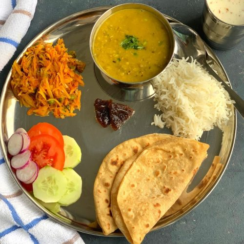 A North Indian Vegetarian lunch thali is a No onion No garlic, simple everyday balanced meal of proteins and carbs from nutritious dal, vegetable, salad, roti and rice.