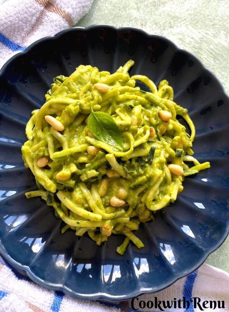The creamy texture of Zucchini pasta, when more of Avocado Dip is added. The pasta is served in a blue round dish with a kitchen towel around.