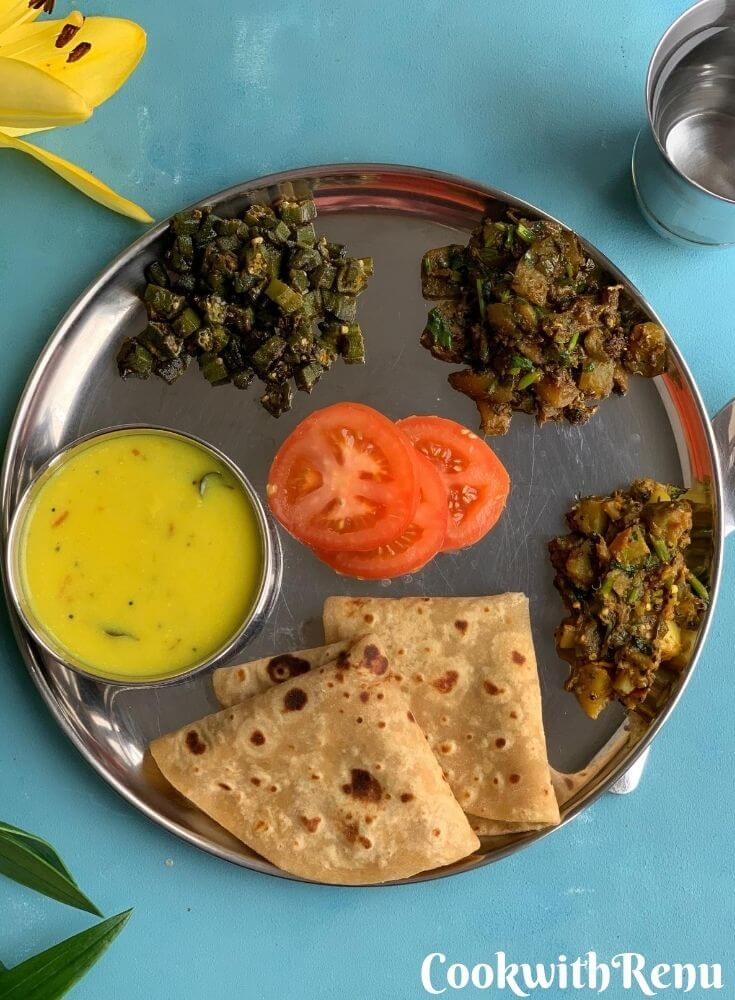 Summer special Vegetarian Thali. Clockwise from 6'o clock served is roti, Kadhi, Bhindi, Watermelon Rind Sabji, Aloo Baingan Sabji. Tomato in centre and a glass filled with water alongside