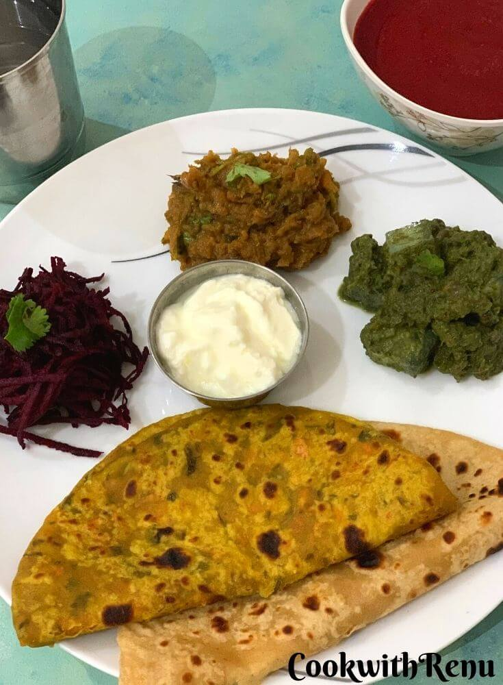 Thali has Clockwise from 6'o clock, 2 Parathas (carrot & Plain), Beetroot Salad, Turnip Bharta, Kale, tofu and corn curry and yogurt in between. Beetroot soup is seen on the side along with a glass of water on the other side.