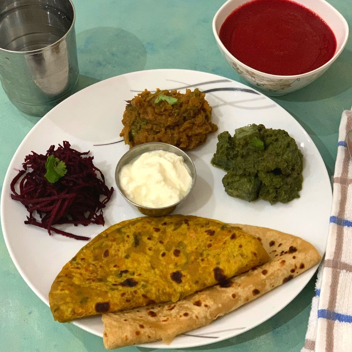 Winter Special Vegetarian Thali has Clockwise from 6'o clock, 2 Parathas (carrot & Plain), Beetroot Salad, Turnip Bharta, Kale, tofu and corn curry and yogurt in between. Beetroot soup is seen on the side along with a glass of water on the other side.