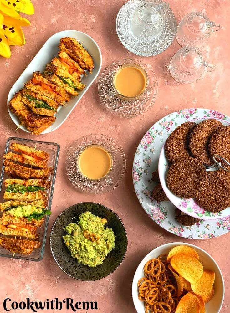 Afternoon Tea Time Platter featuring different types of Vegan Sandwiches, Gluten-Free and nut-free cookies, chips, and dips catering to people with different food groups.