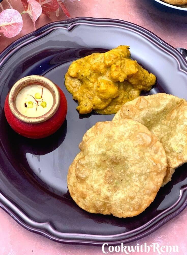 Close up look of Bengali Breakfast thali in a plate with Koraishutir Kochuri, Niramish Aloo Dum, and Mishti Doi.