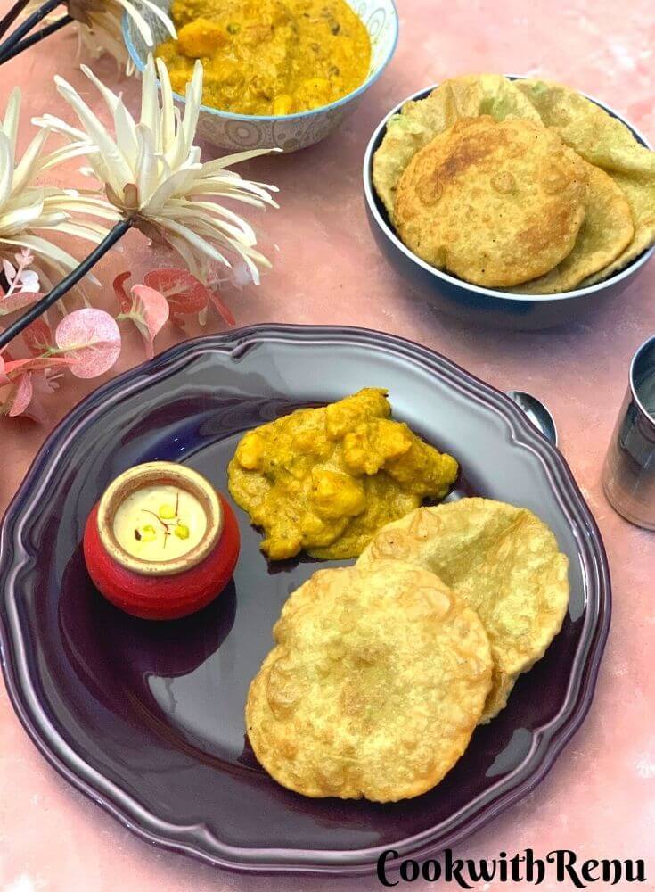 Bengali Breakfast thali presented in a plate with Koraishutir Kochuri, Niramish Aloo Dum, and Mishti Doi. Seen are some artificial flowers, a bowl full of kachori and another bowl with bhaji