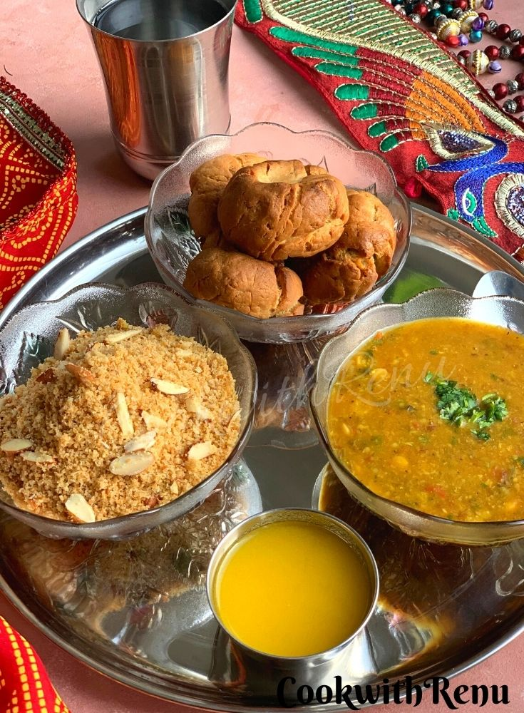 Rajasthani Dal Baati churma presented in a thali, along with some ghee (clarified butter) and water.