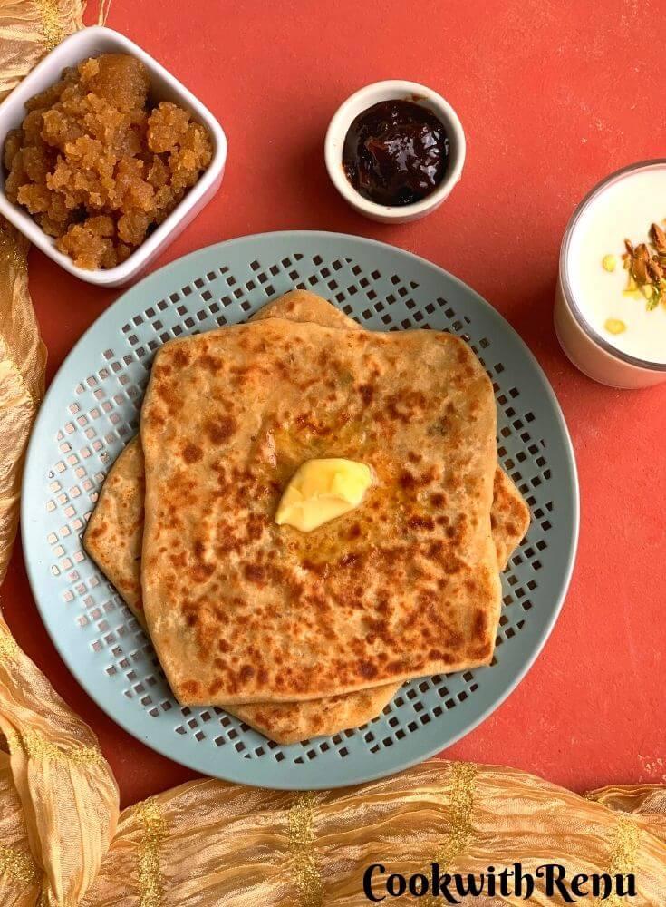Easy Mooli Paratha served with a dollop of butter, no oil lemon pickle, Sweet Lassi (Yogurt drink) and Ate ka halwa/karah Prasad