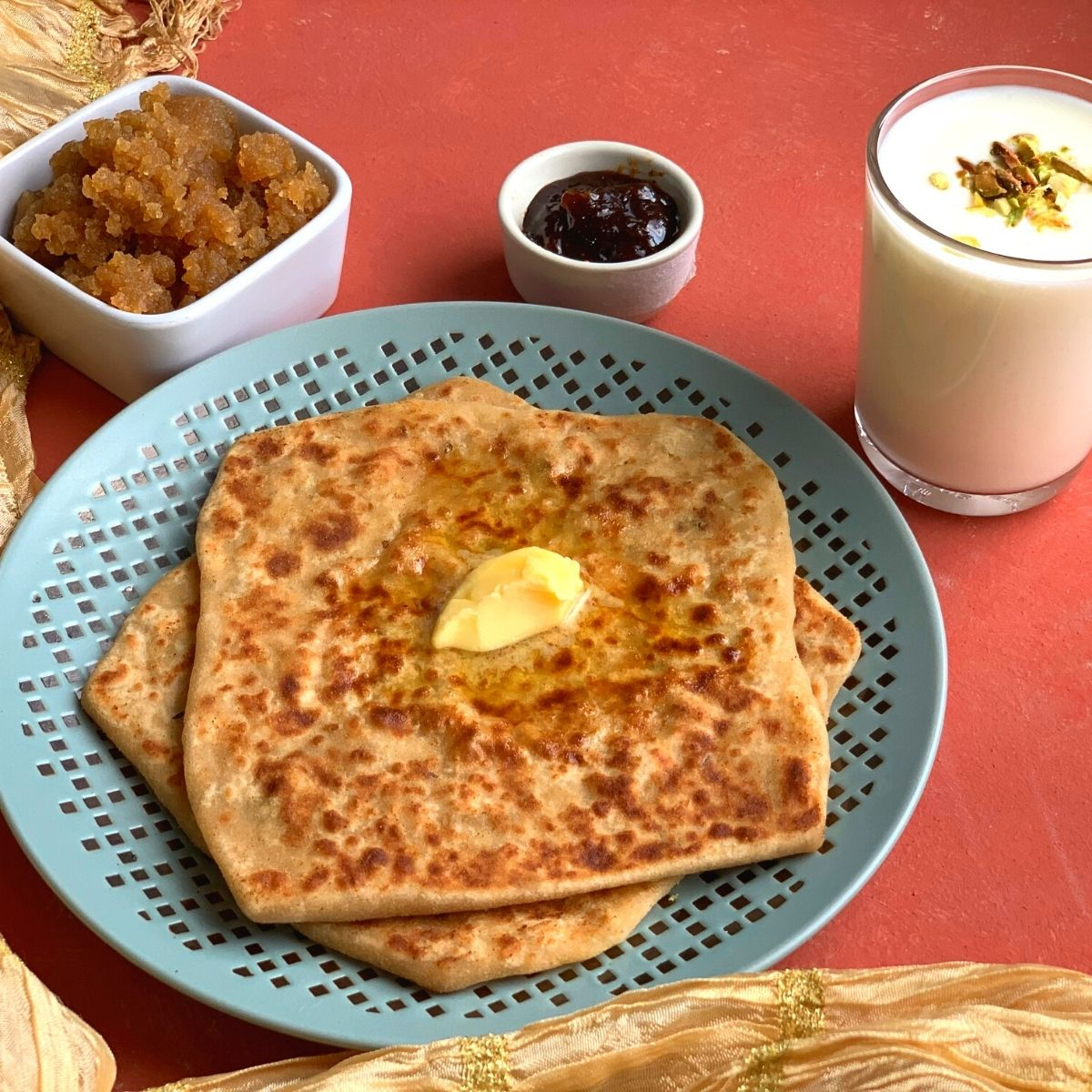 Easy Daikon Paratha served with a dollop of butter, no oil lemon pickle, Sweet Lassi (Yogurt drink) and Ate ka halwa/karah Prasad