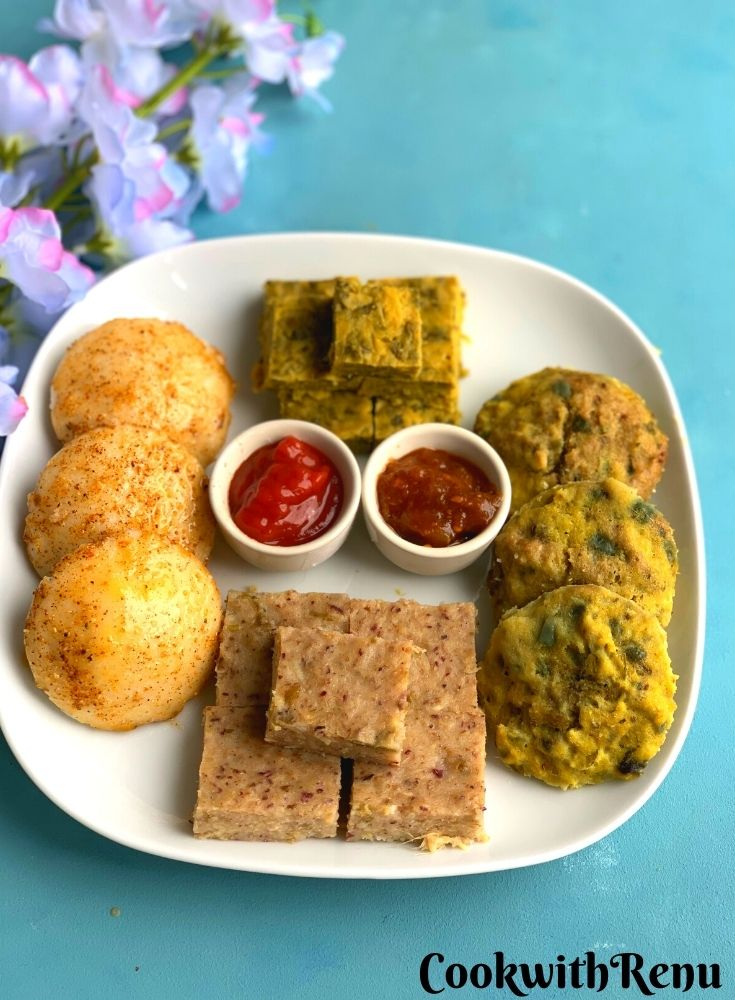 Easy Steamed Meal Platter has Four Steamed Dishes Idli, Kothimbir Vadi, Chana Dal Bafuri, and Dhokla are presented in a white square plate with Tomato chutney and tomato sauce. Seen in the background are some flowers.