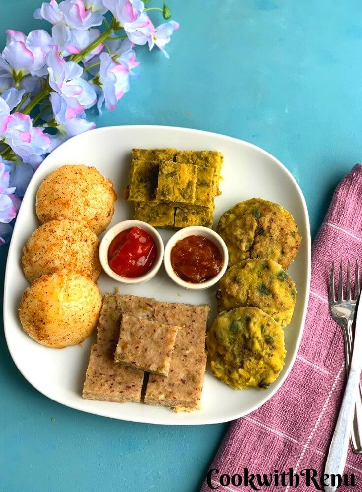 Easy Steamed Meal Platter has Four Steamed Dishes Idli, Kothimbir Vadi, Chana Dal Bafuri, and Dhokla are presented in a white square plate with Tomato chutney and tomato sauce. Seen in the background are some flowers, fork and knife with a clean napkin