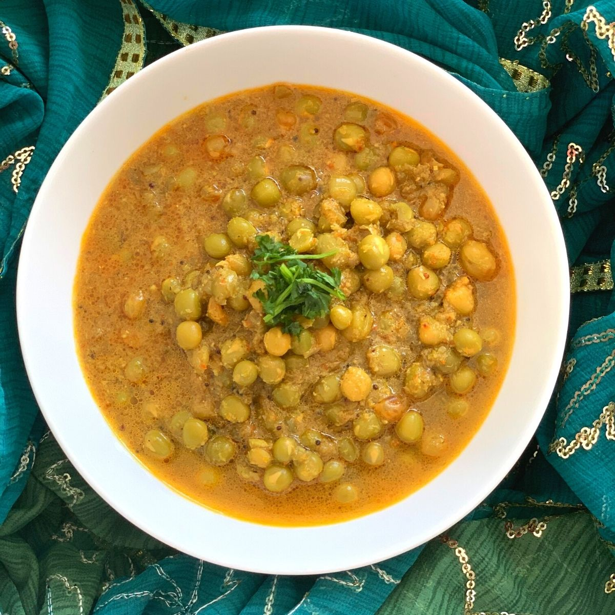 Goan Green Peas Curry served in a white bowl and garnished with coriander. A green stole is seen in the background