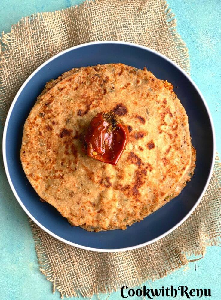 Gobi Paratha served on a blue plate with pickle on top of it. Seen at the bottom is a jute cloth