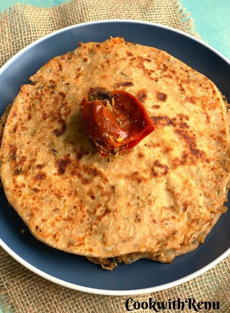 Close up look of Gobi paratha with pickle on top of it