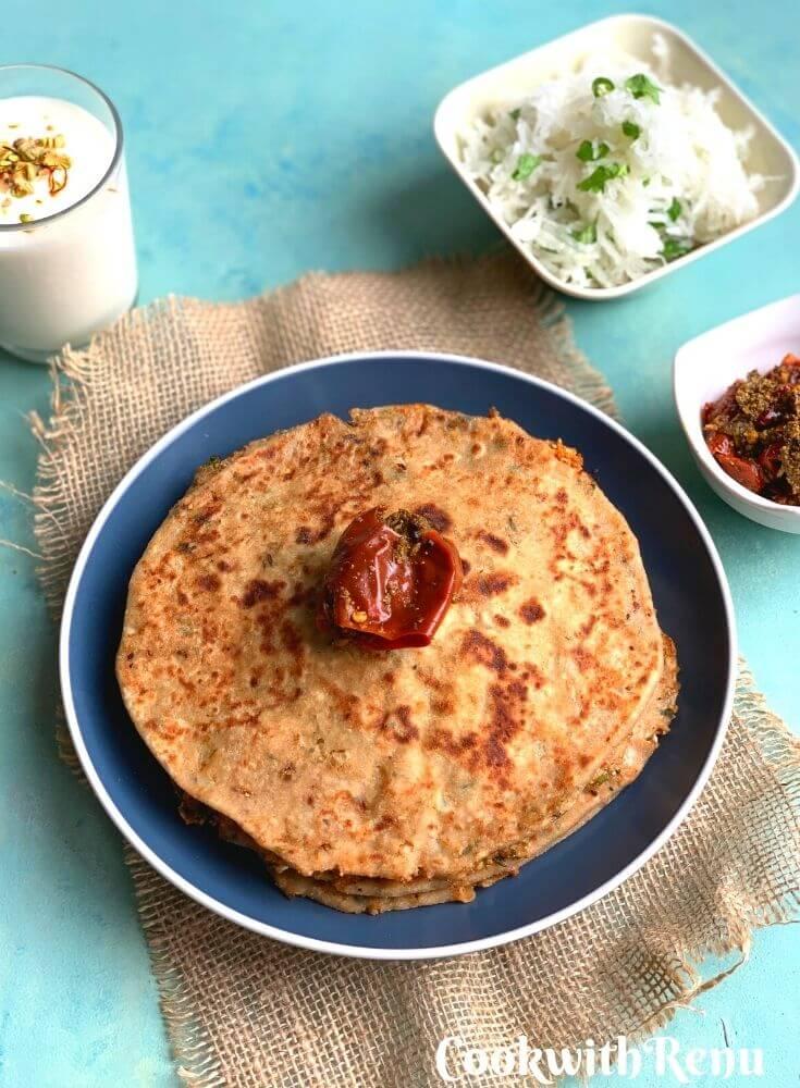 The Breakfast thali is served on a blue plate with Gobi paratha, mooli salad, pickle and yogurt lassi