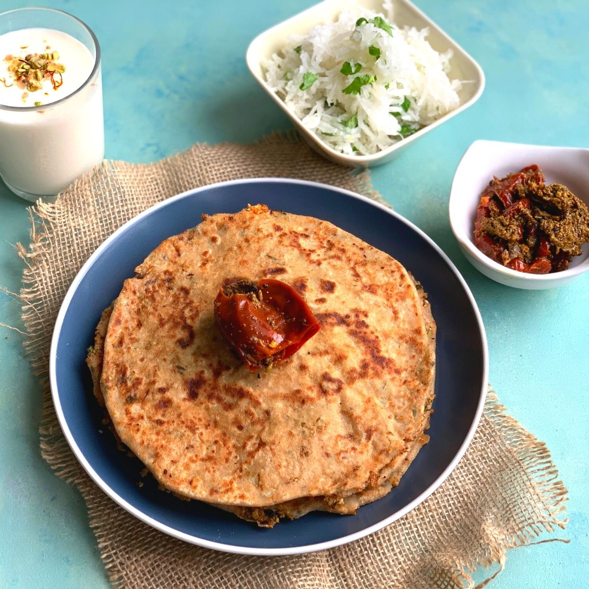 Gobi Paratha is a healthy breakfast and lunch box recipe where the flatbread is stuffed with gobi i.e. cauliflower and a few spices. The Breakfast thali is served with paratha, mooli salad, pickle and yogurt lassi