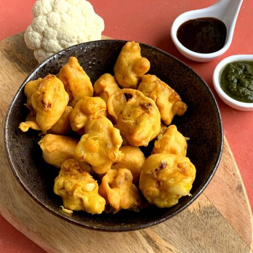 Gobi pakora or Cauliflower pakoda is an irresistible and addictive tea time fritter which are crunchy on the outside, soft inside and perfect as a party appetizer. They are served in a black bowl with 2 chutneys, coriander and tamarind.