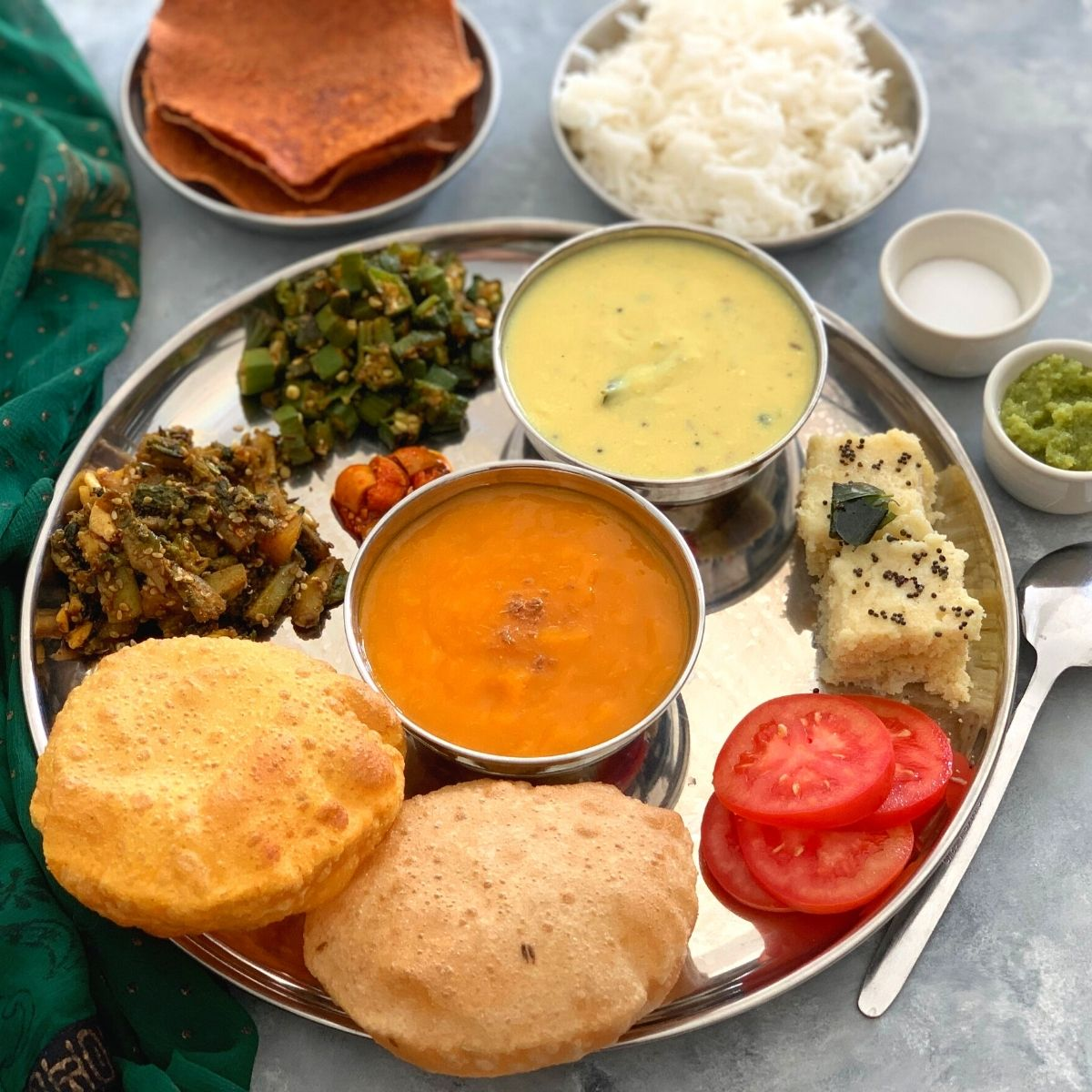 Gujarati Thali is a spectacular treat and fusion of sweet, salty, and spicy flavors all combined in a classic Indian Regional thali.