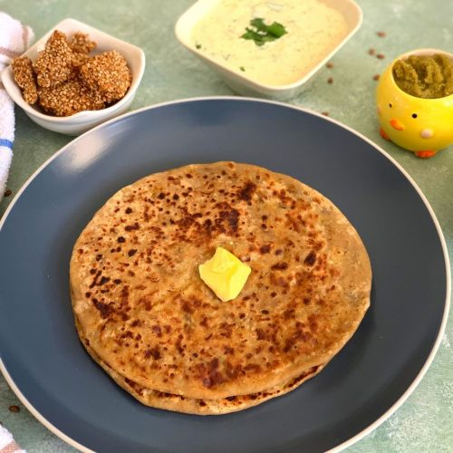 Horse Gram paratha served on a blue plate along with cucumber raita, til chikki, amla dhaniya chutney and slices of cucumber