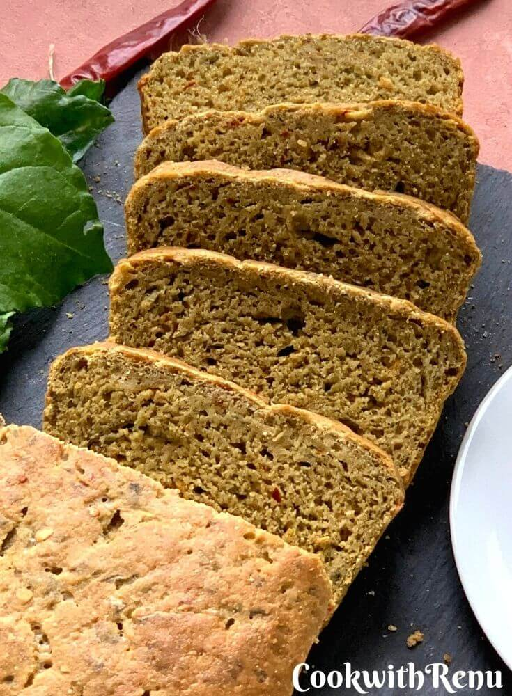 Close up look of the bread with slices cut. Texture of the bread can be seen closely with some spinach and red chilly flakes on the side