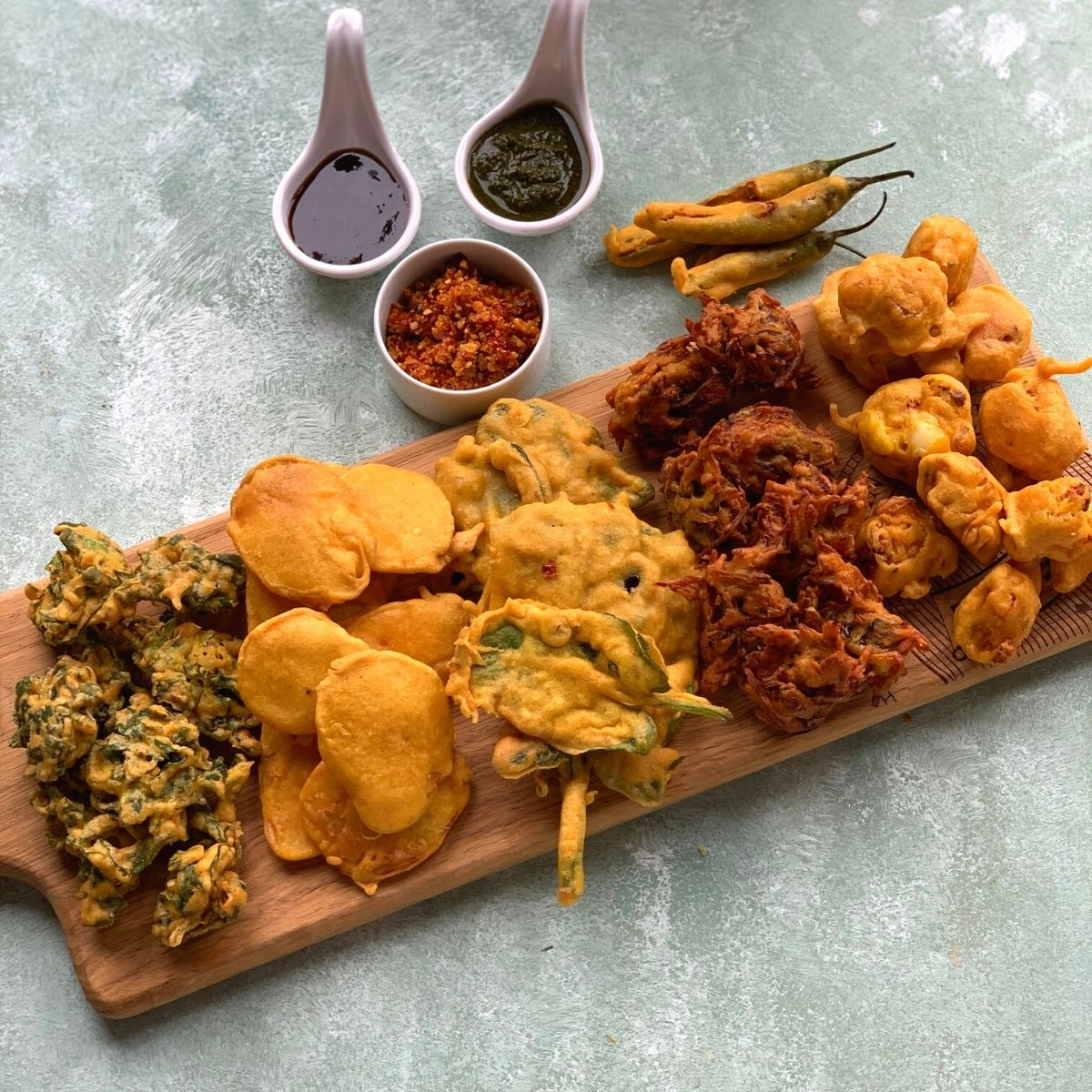 Tea time Pakora Platter is an addictive platter which has 6 different types of pakoras. They are yummy and crunchy snack or tea time fritters. Fritters are served on a wooden board with Coriander, Imli and Garlic chutneys on the side.