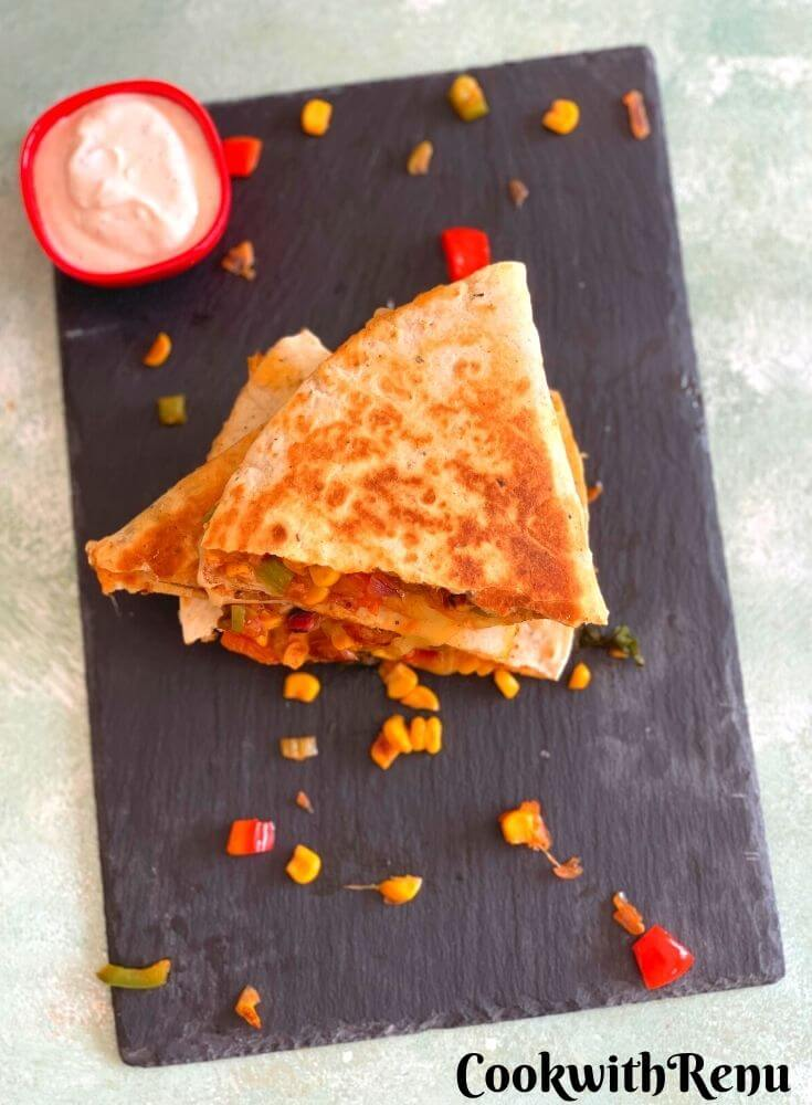 Vegetarian quesadilla arranged on a black serving board with a yogurt dip. They have been stocked one above the other