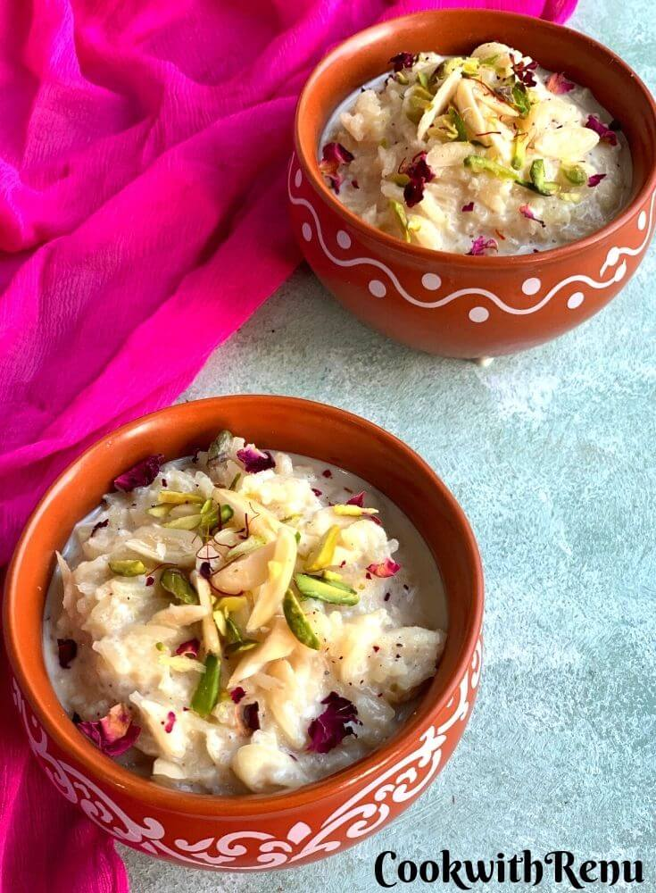 Rice kheer presented in 2 designer brown bowls, garnished with almonds, pistachio, saffron and edible rose petals
