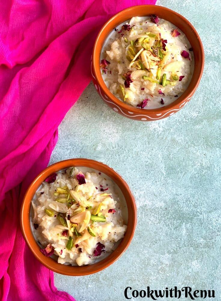 Indian Rice Pudding presented in 2 designer brown bowls, garnished with almonds, pistachio, saffron and edible rose petals