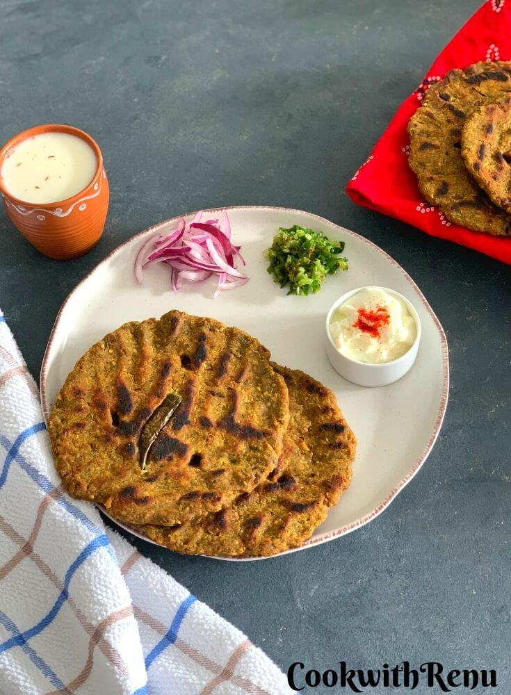 Multi flour Flatbread served in a white plate with yogurt, green chilly and onion along with some buttermilk