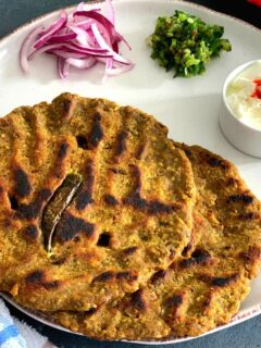 Close up look of Thalipeeth served in a white plate with yogurt, green chilly and onion.