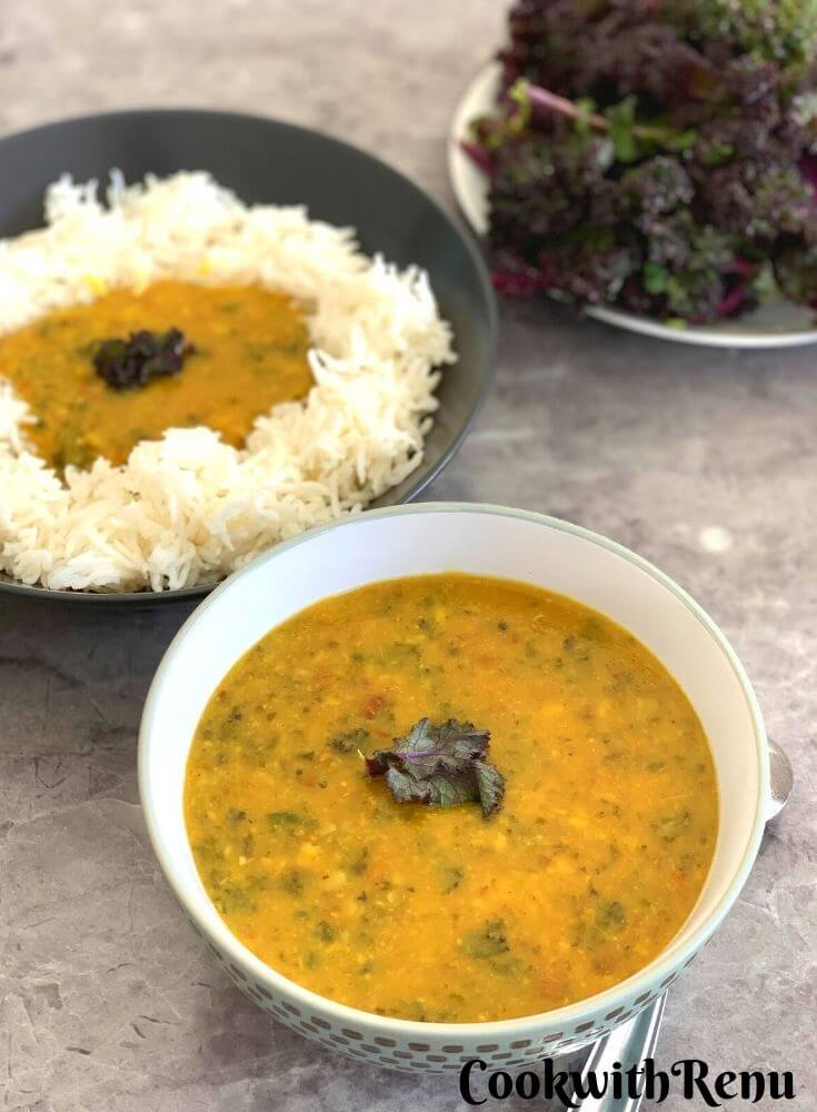 Kale dal presented in a big bowl, with kale and another rice and dal bowl seen in background