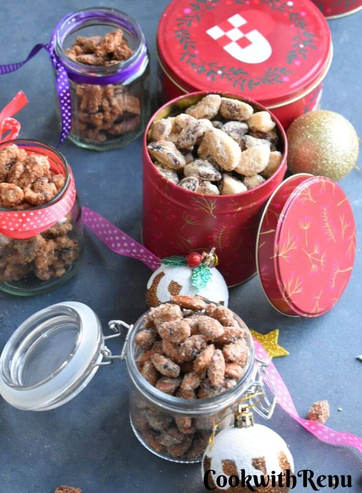 Mixed Spiced Nuts presented as edible gifts in glass jar and tins with some Christmas decorations