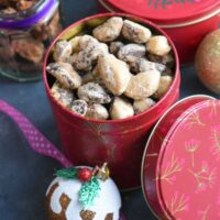 Spiced Brazil nuts in a gift tin with some Christmas Decorations seen on the side