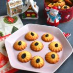 Spritz Cookies or Swedish Butter cookies are crispy, buttery cookies from the Scandinavia Cuisine and a must during Christmas. They are served on a pink plate with Snowman and Christmas decorations seen in background.
